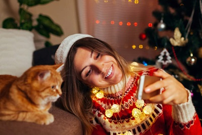 woman taking cell phone photo with cat